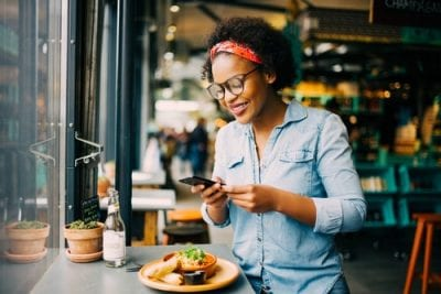 Young African American woman smiling looking at restaurant deals on phone