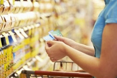woman in supermarket with coupon